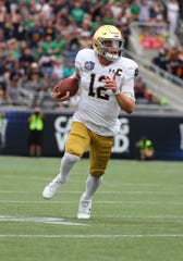 Dec 28, 2019; Orlando, Florida, USA;Notre Dame Fighting Irish quarterback Ian Book (12) runs with the ball against the Iowa State Cyclones during the first quarter at Camping World Stadium. Mandatory Credit: Kim Klement-USA TODAY Sports
