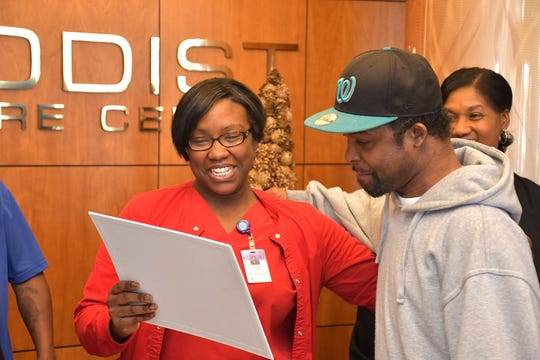 As part of Michael Jordan's festive send-off on Dec. 18, 2019, Methodist Specialty Care Center Activities Director Courtney Jones presents him with a card signed by staff and other residents.