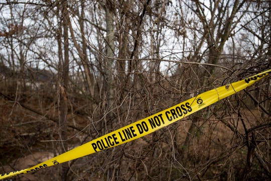 A police tape is stretched across the trees  on the westbound side of Oil Well Road. Police search in the wooded area where human remains were found on Wednesday Dec. 25, 2019.  as police searched the wooded area were human remains were found on Wednesday Dec. 25, 2019.