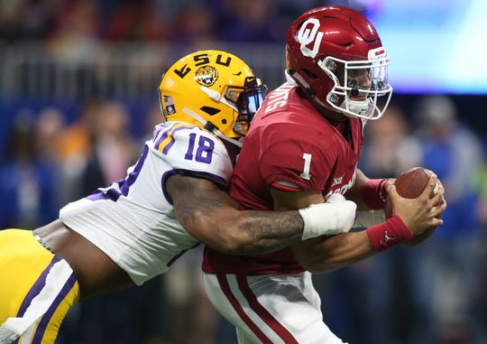 Dec 28, 2019; Atlanta, Georgia, USA; Oklahoma Sooners quarterback Jalen Hurts (1) is sacked by LSU Tigers linebacker K'Lavon Chaisson (18) during the first quarter of the 2019 Peach Bowl college football playoff semifinal game. Mandatory Credit: Brett Davis-USA TODAY Sports