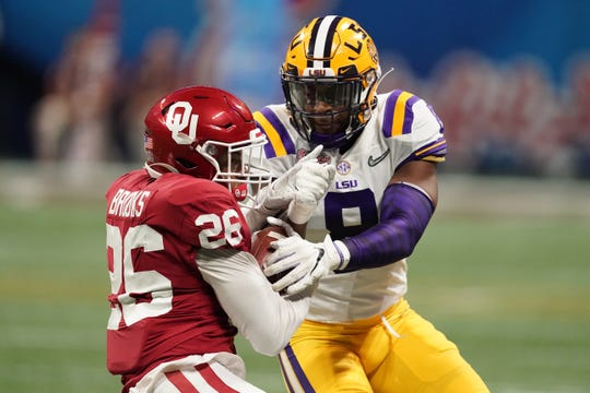 Dec 28, 2019; Atlanta, Georgia, USA;  Oklahoma Sooners running back Kennedy Brooks (26) runs the ball against LSU Tigers linebacker Patrick Queen (8) during the second quarter of the 2019 Peach Bowl college football playoff semifinal game. Mandatory Credit: John David Mercer-USA TODAY Sports