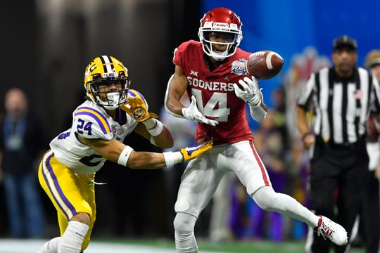 Oklahoma wide receiver Charleston Rambo (14) misses a catch against LSU cornerback Derek Stingley Jr. (24) during the first half of the Peach Bowl NCAA semifinal college football playoff game, Saturday, Dec. 28, 2019, in Atlanta. (AP Photo/John Amis)