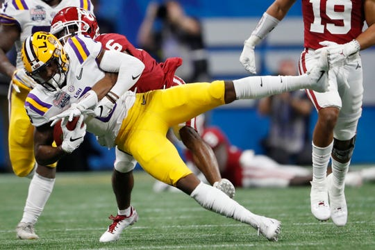 LSU wide receiver Terrace Marshall Jr. (6) makes the catch ahead of Oklahoma cornerback Tre Brown (6) during the first half of the Peach Bowl NCAA semifinal college football playoff game, Saturday, Dec. 28, 2019, in Atlanta. (AP Photo/John Bazemore)