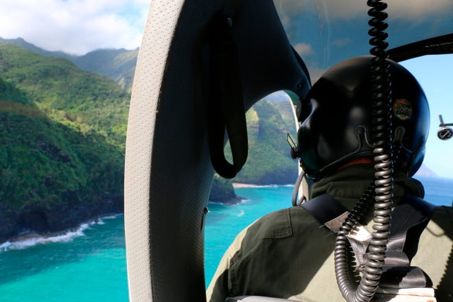 This photo provided by the Hawaii Department of Land and Natural Resources shows a Coast Guard search and rescue team looking over Napali Coast State Wilderness Park for a tour helicopter that disappeared in Hawaii with seven people aboard Friday.