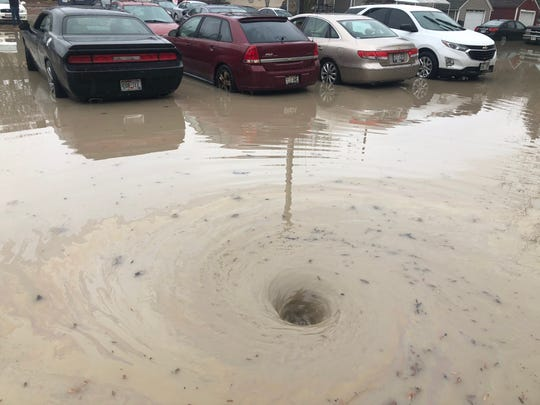Floodwater circles a drain in the parking lot at Hawley Terrace Apartments after a water main break.