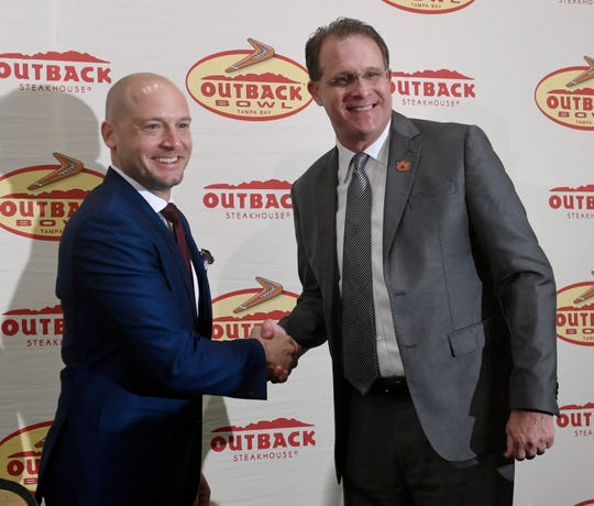 Auburn coach Gus Malzahn (left) and Minnesota coach P.J. Fleck (right) speak at an Outback Bowl press conference on Saturday, Dec. 28, 2019, in Tampa, Florida.