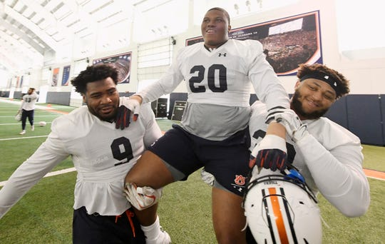 Senior Derrick Brown (wearing Jeremiah Dinson's No. 20 jersey) gets carried off the field after his last practice in Auburn on Saturday, Dec. 21, 2019 in Auburn, Ala.