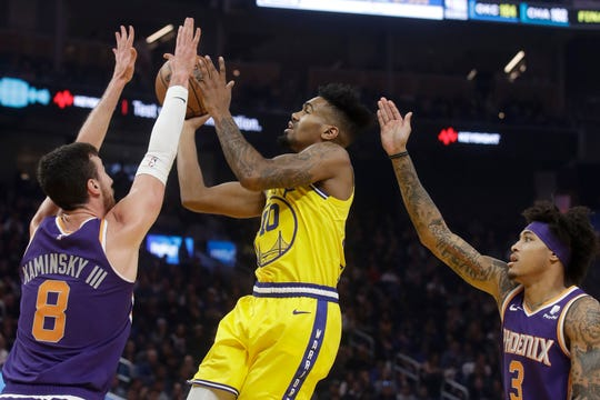 Golden State Warriors guard Jacob Evans III, center, shoots between Phoenix Suns forwards Frank Kaminsky III (8) and Kelly Oubre Jr. (3) during the first half of an NBA basketball game in San Francisco, Friday, Dec. 27, 2019. (AP Photo/Jeff Chiu)