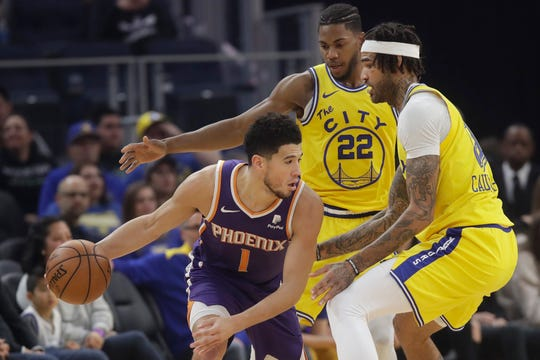 Phoenix Suns guard Devin Booker (1) is is defended by Golden State Warriors forward Glenn Robinson III (22) and center Willie Cauley-Stein during the first half of an NBA basketball game in San Francisco, Friday, Dec. 27, 2019. (AP Photo/Jeff Chiu)