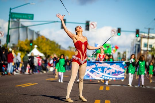 Molly Johnson of Arizona Twirling Athletes Show Corps twirls batons at the Fiesta Bowl Parade in Phoenix on Saturday, Dec. 28, 2019.