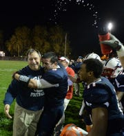 Mark Pyles, right, celebrates Lebanon's district playoff-clinching win over Elizabethtown with assistant coach Bud Getz, left, and teammate and close friend Jeremy De La Cruz back in 2013.