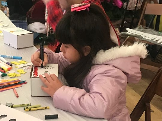 Mia Gomez, 8, draws on a box that is part of the Three Kings' Day at Roc Holiday Village on Saturday.