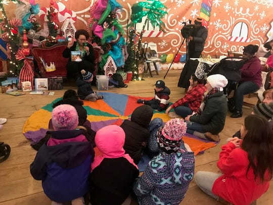 Stephanie Paredes reads to children at the Three Kings' Day celebration at Roc Holiday Village.