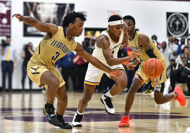 University Prep's Na'Zea Fowlks, center, splits the defense of Leadership Academy's Calvin Washington, left, and Shamir McCullough during the Mike Dianetti Classic at Aquinas Institute, Friday, Dec. 27, 2019. Leadership Academy beat University Prep 80-78 in overtime.