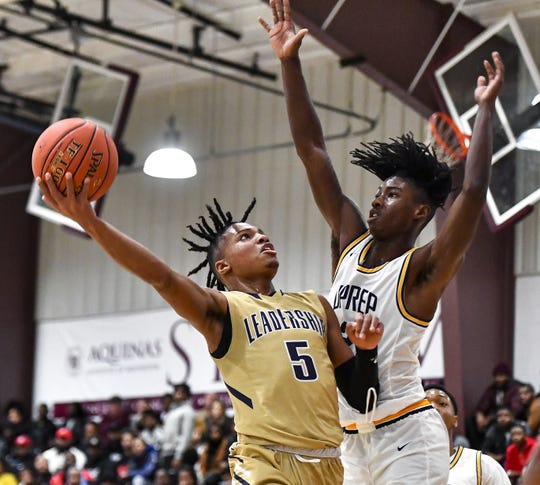 Leadership Academy's Maurice McKinney, left, is defended by University Prep's Christian Edwards during the Mike Dianetti Classic at Aquinas Institute in December. McKinney has delivered several clutch plays for the Lions (14-2)  this season.