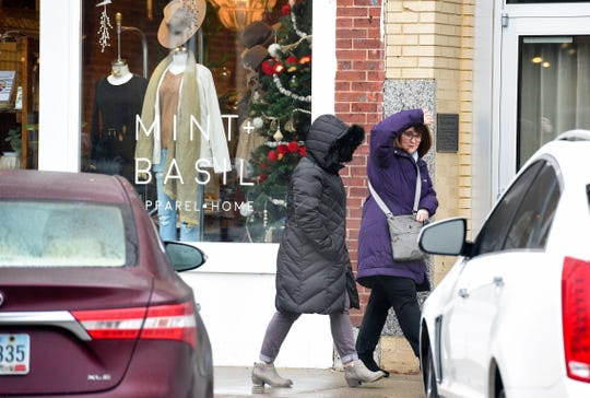 Shoppers downtown shield themselves from the persistent light rain as they exit a shop on Saturday, Dec. 28, in Sioux Falls.