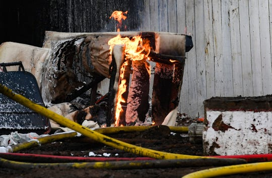 Flames lick the side of a couch leftover from a house fire on Friday, Dec. 27, on east 6th Street in Sioux Falls.