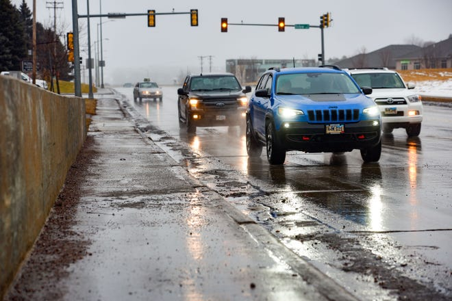 Drivers keep their headlights on to stay safe in the gray, slick road conditions on Saturday, Dec. 28, in Sioux Falls. It is gray and sad outside.
