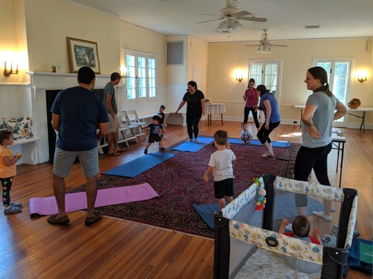 KC Knudsen leads little yogis in learning their first yoga moves.