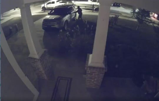 A screenshot from a video taken about 2 a.m. in the same neighborhood as a shooting shows two cars driving slowly as three people jump out and test car handles.
