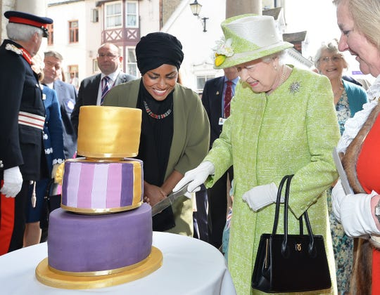Queen Elizabeth II receives a birthday cake from Nadiya Hussain, winner of the Great British Bake Off, during her 90th Birthday Walkabout on April 21, 2016 in Windsor.