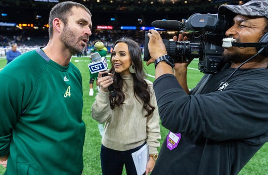 Carley McCord, middle, interviews Acadiana High School football coach Scott McCullough after the Louisiana  Division 5A championship game Saturday, Dec. 14, 2019.