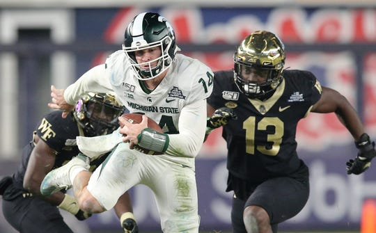 Pinstripe Bowl: Michigan State quarterback Brian Lewerke runs the ball after making a move against defensive back Trey Rucker (18).