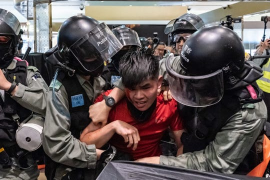 "A man is detained by riot police during a demonstration in a shopping mall at Sheung Shui district on December 28, 2019 in Hong Kong, China. Anti-government protesters in Hong Kong continue their demands for an independent inquiry into police brutality, the retraction of the word ""riot"" to describe the rallies, and genuine universal suffrage."