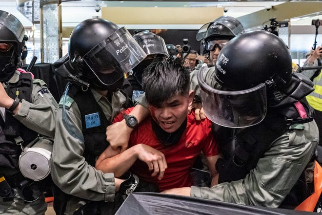 """A man is detained by riot police during a demonstration in a shopping mall at Sheung Shui district on December 28, 2019 in Hong Kong, China. Anti-government protesters in Hong Kong continue their demands for an independent inquiry into police brutality, the retraction of the word """"riot"""" to describe the rallies, and genuine universal suffrage."""
