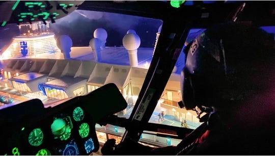 U.S. Coast Guard crew fly above the Anthem of the Seas cruise ship to pick up a passenger suffering severe abdominal pain on Saturday.