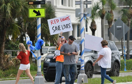 People walk back and forth over the pedestrian crosswalk at the corner of Ellwood Avenue and A1A  Dec. 28 in Satellite Beach. The group of nearly 100 was there to draw attention to the pedestrian crosswalk installed at the intersection and to advocate for a different kind of warning system after the death of 12-year-old Sophia Nelson. She was struck and killed by a vehicle Dec. 22 despite the newly installed warning lights at the intersection.
