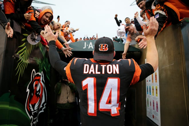 Cincinnati Bengals quarterback Andy Dalton (14) recognizes the fans at the conclusion of an NFL Week 17 game against the Cleveland Browns, Sunday, Dec. 29, 2019, at Paul Brown Stadium in Cincinnati. Cincinnati Bengals won 33-23.