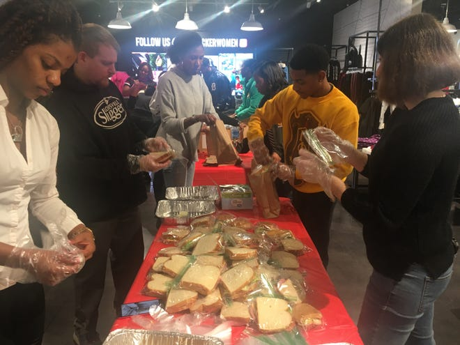 "Kellie Stark, right, of Farmington, and other volunteers prepare sandwiches for Hashtag Lunchbag's ""Holiday Giveback"" event at the Foot Locker Community Store in Eastpointe on Sunday."