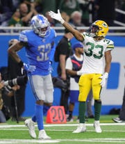 Green Bay Packers running back Aaron Jones celebrates a first down against Detroit Lions safety Tavon Wilson during the final minutes of the fourth quarter Sunday, Dec. 29, 2019 at Ford Field.