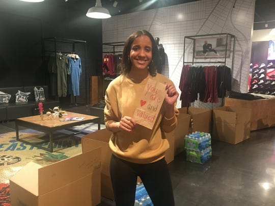"Alayna Washington of Chicago volunteers at the Hashtag Lunchbag ""Holiday Giveback"" event at the Foot Locker Community Store in Eastpointe on Sunday."