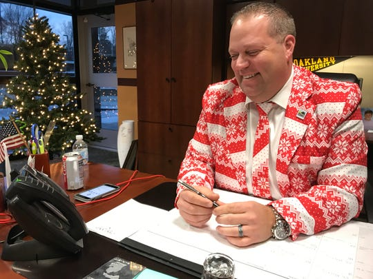 Rochester Hills Mayor Bryan Barnett, in Christmas attire for City Hall's annual holiday party, speaks on the phone to New York City Mayor Bill de Blasio on Dec. 10.