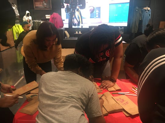 "Volunteers write words of affirmation on lunch bags for Hashtag Lunchbag's ""Holiday Giveback"" event at the Foot Locker Community Store in Eastpointe on Sunday."