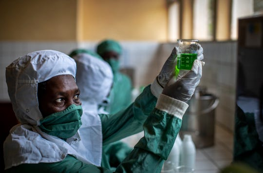 In this photo taken Thursday, Nov. 7, 2019, workers wearing protective clothing to protect from the effects of the drug and to prevent contamination, make liquid morphine from powder which is dyed green as a color-code to indicate the strength, at the Pharmaceutical Laboratory of Rwanda in Butare, Rwanda.