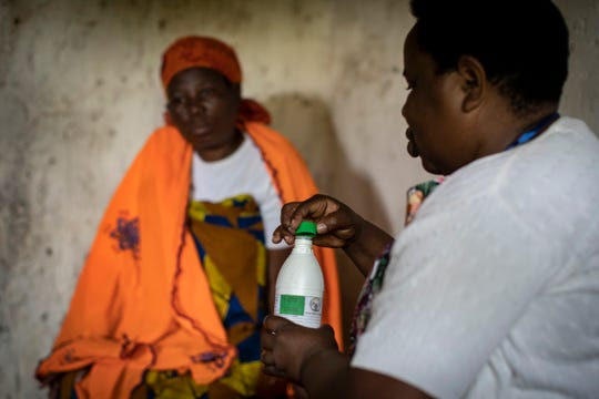 In this photo taken Tuesday, Nov. 5, 2019, palliative care nurse Madeleine Mukantagara, 56, right, prepares to give an increased dose of oral liquid morphine to Faina Nyirabaguiza, 52, left, who has cervical cancer, during a visit to check on her health at her home in the village of Ruesero, near Kibogora, in western Rwanda.