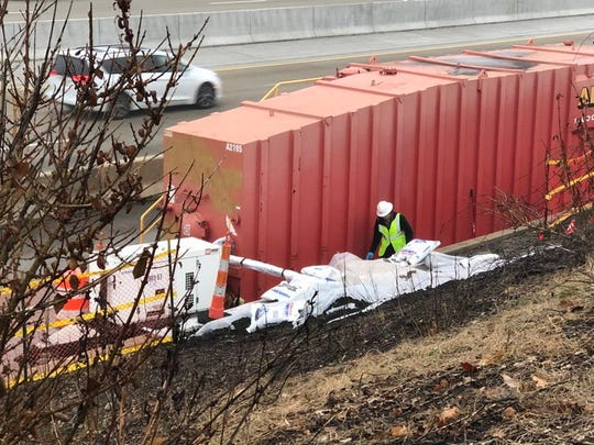 An EPA contractor checks on the sump pump siphoning water from the embankment where contaminated liquid from a shuttered plating facility seeped onto the I-696 shoulder earlier this month.