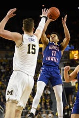 UMass Lowell guard Obadiah Noel  shoots over Michigan center Jon Teske.