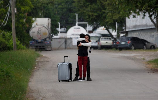 A man who was deported from the United States, foreground, is welcomed by a relative outside the Ramon Villeda International Airport in La Lima, Honduras on Nov. 29, 2019.