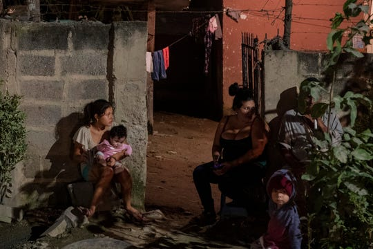 A  family sits outside their home as forensic workers investigate a body at a crime scene in the Rivera Hernandez neighborhood of San Pedro Sula, Honduras on Nov. 30, 2019.