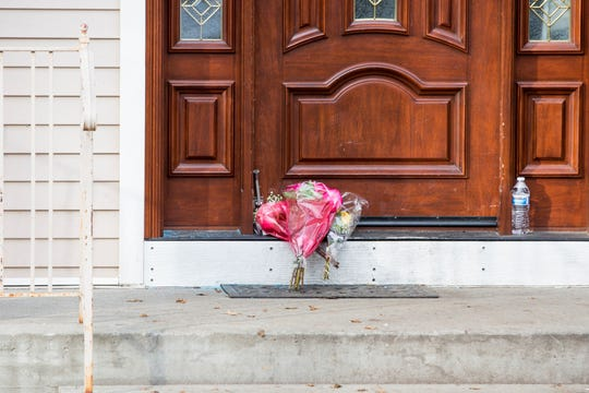 Flower bouquets rest on the doorstep of a rabbi's residence in Monsey, N.Y., Sunday, Dec. 29, 2019.
