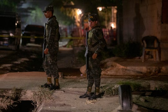 Soldiers stand guard near a crime scene Nov. 30, 2019, as forensic workers inspect a body in the Rivera Hernandez neighborhood of San Pedro Sula, Honduras.