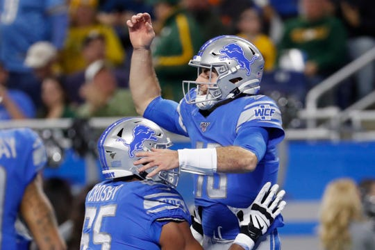 Lions quarterback David Blough is lifted by teammate offensive tackle Tyrell Crosby after scoring on a 19-yard pass from Danny Amendola.