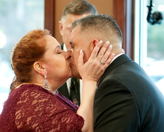 Newlyweds Valerie Sneade and Jason Roy kiss during their wedding ceremony at the Dunkin' Donuts on Friday, Dec. 27, 2019 in Worcester, Mass.