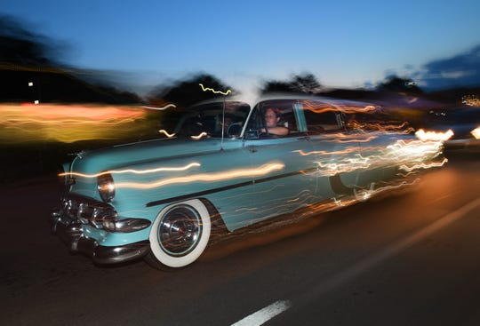 A classic car trails a blur of headlights while cruising Woodward Avenue in Royal Oak Friday night, August 16, 2019 before Saturday's Woodward Dream Cruise.