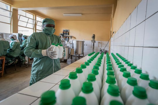 In this photo taken Thursday, Nov. 7, 2019, a worker carries bottles of liquid morphine after making it from powder, wearing protective clothing to protect from the effects of the drug and to prevent contamination, at the Pharmaceutical Laboratory of Rwanda in Butare, Rwanda.