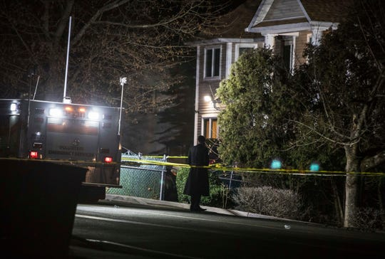 An Orthodox Jewish man stands in front of a residence in Monsey, N.Y., Sunday  following a stabbing late Saturday during a Hanukkah celebration.
